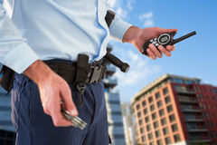 Composite image of mid section of security officer holding hand cuff and walkie talkie Stock Photos