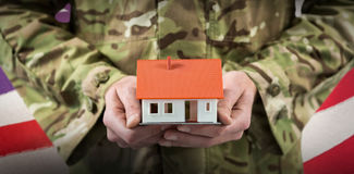 Composite image of mid section of soldier holding model home. Mid section of soldier holding model home against waving flag of america royalty free stock photography