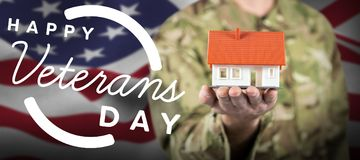 Composite image of mid section of soldier holding model house. Mid section of soldier holding model house against focus on usa flag Stock Images