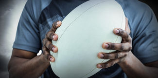 Composite image of mid section of sportsman holding rugby ball Royalty Free Stock Images