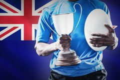 Composite image of mid section of sportsman holding trophy and rugby ball Royalty Free Stock Images