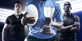 Composite image of mid section of sportsman holding trophy and rugby ball Royalty Free Stock Image