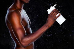 Composite image of mid section of a sporty young man holding protein drink stock illustration