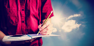 Composite image of mid section of student with mobile phone writing on notebook. Mid section of student with mobile phone writing on notebook  against cloudy sky Royalty Free Stock Images