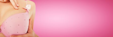 Composite image of mid section of woman wearing pink bra for breast cancer awareness Royalty Free Stock Images