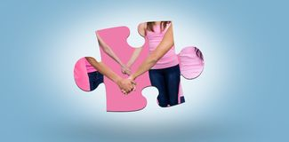 Composite image of mid section of women in pink outfits holding hands while standing for breast canc Royalty Free Stock Images
