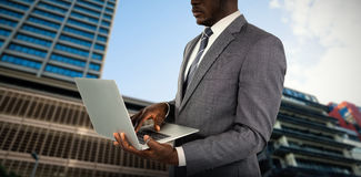 Composite image of midsection of businessman using laptop. Midsection of businessman using laptop against building against cloudy sky Stock Photo