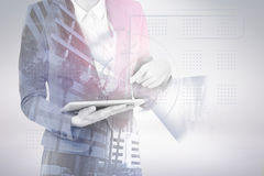 Composite image of midsection of businesswoman using digital tablet 3d. Midsection of businesswoman using digital tablet against buildings in city 3d Stock Images