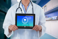 Composite image of midsection of female doctor holding digital tablet Stock Photo