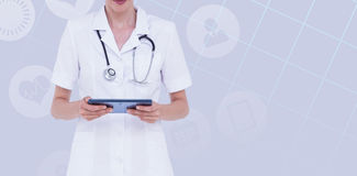 Composite image of midsection of female doctor using tablet computer. Midsection of female doctor using tablet computer against pastel blue Royalty Free Stock Image