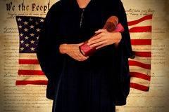 Composite image of midsection of female lawyer holding gavel and book. Midsection of female lawyer holding gavel and book against declaration of independence Royalty Free Stock Images