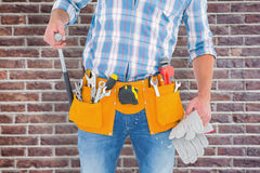 Composite image of midsection of handyman holding hammer and gloves Stock Images