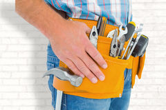 Composite image of midsection of handyman wearing tool belt. Midsection of handyman wearing tool belt against white wall stock images