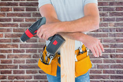 Composite image of midsection of male carpenter with power drill and plank Royalty Free Stock Photos