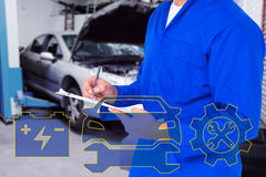 Composite image of midsection of mechanic writing on clipboard. Midsection of mechanic writing on clipboard against workshop stock photos