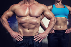 Composite image of midsection of muscular man and woman standing with hands on hip Royalty Free Stock Photo