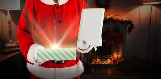 Composite image of midsection of santa claus opening gift box. Midsection of Santa Claus opening gift box against fireplace decorate with christmas decor and Stock Image