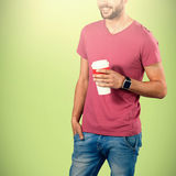 Composite image of midsection of smiling model holding disposable coffee cup. Midsection of smiling model holding disposable coffee cup against green background Stock Photo