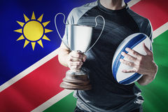 Composite image of midsection of successful rugby player holding trophy and ball Stock Image