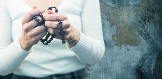 Composite image of midsection of woman holding rosary beads. Midsection of woman holding rosary beads against rusty weathered wall royalty free stock images