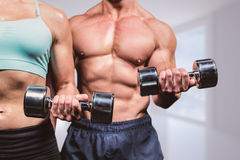 Composite image of midsection of woman and man exercising with dumbbells Stock Image