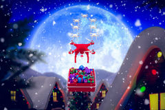 Composite image of mini drone pulling chirstmas sledge. Mini drone pulling Chirstmas sledge against christmas village under full moon Royalty Free Stock Photography
