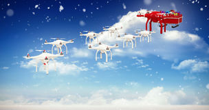 Composite image of mini drones pulling chirstmas sledge with gift Stock Images