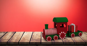 Composite image of miniature train with gift Royalty Free Stock Image