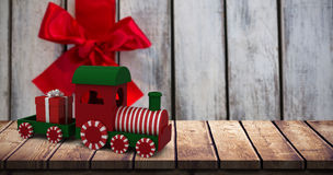 Composite image of miniature train with gift Stock Photos