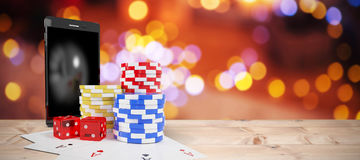 Composite image of mobile phone with stack of gambling chips and playing cards Royalty Free Stock Photo