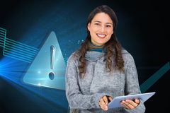 Composite image of model wearing winter clothes holding her tablet Stock Photos