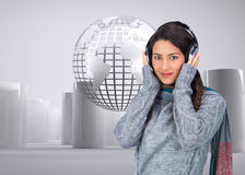 Composite image of model wearing winter clothes listening to music Stock Photo