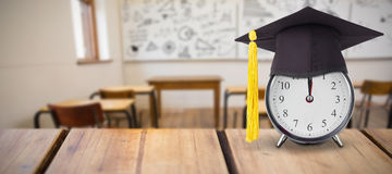 Composite image of mortar board on alarm Royalty Free Stock Images