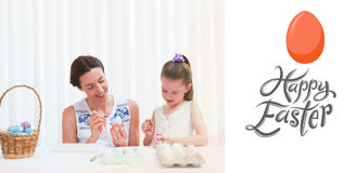 Composite image of mother and daughter painting easter eggs Stock Photos