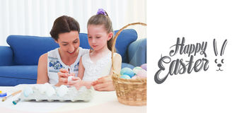 Composite image of mother and daughter painting easter eggs Royalty Free Stock Photos