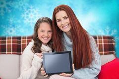 Composite image of mother and daughter showing tablet Stock Image