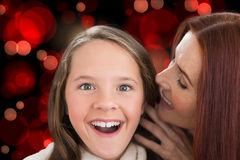 Composite image of mother and daughter telling secrets Royalty Free Stock Photos