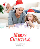 Composite image of mother and daughter unwrapping a present lying on the floor Stock Image