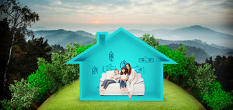 Composite image of mother with their children sitting on sofa. Mother with their children sitting on sofa against trees and mountain range against cloudy sky Royalty Free Stock Photo