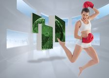 Composite image of motivated fit brown haired model in sportswear jumping Stock Image
