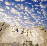 Composite image of Mount Rushmore and blue sky with white puffy clouds Stock Images