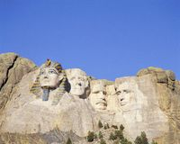Composite image of Mt. Rushmore with Washington replaced by an Egyptian Pharaoh against blue sky Stock Images