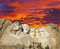 Composite image of Mt. Rushmore with Washington replaced by an Egyptian Pharaoh against dark sky with orange sunset clouds Royalty Free Stock Images