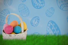 Composite image of mulit colored easter eggs in wicker basket Stock Photos