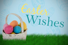 Composite image of mulit colored easter eggs in wicker basket Royalty Free Stock Photos