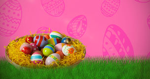 Composite image of multi colored easter eggs in wicker basket Stock Photography