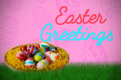 Composite image of multi colored easter eggs in wicker basket Stock Photos