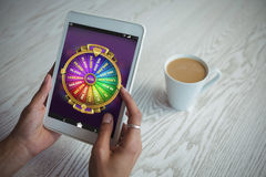 Composite image of multi colored fortune of wheel on mobile display. Multi colored fortune of wheel on mobile display against cropped hands of woman holding Royalty Free Stock Photography