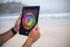 Composite image of multi colored fortune of wheel on mobile display. Multi colored fortune of wheel on mobile display against cropped image of man using tablet Royalty Free Stock Image
