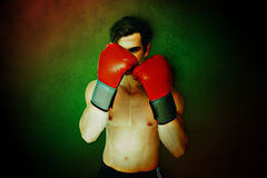 Composite image of muscly man wearing red boxing gloves in guard position Royalty Free Stock Image